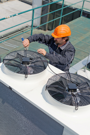 Air Conditioning Repair, repairman on the roof fixing huge air conditioning system photo