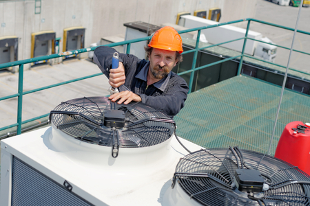 man in air: Air Conditioning Repair, repairman on the roof fixing huge air conditioning system