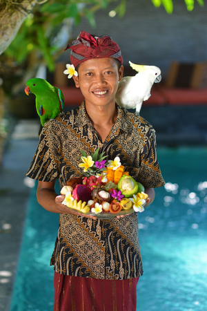 Asian waiter with a tray of tropical fruits in an exotic setting photo