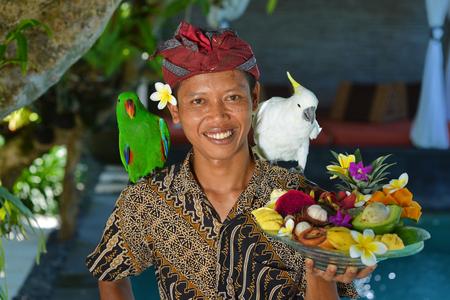 Asiatische Kellner mit einem Tablett von tropischen Früchten in einer exotischen Umgebung Lizenzfreie Bilder