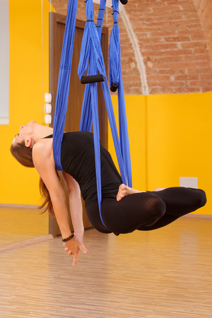 Woman doing anti gravity Aerial yoga exercise  photo