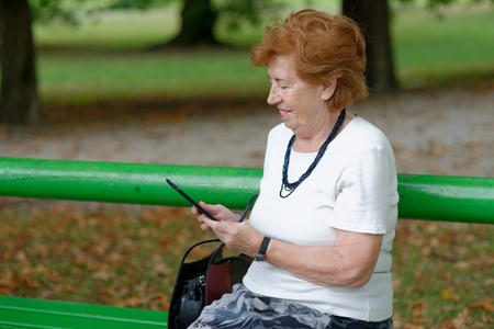 Senior Woman reading E-Book reader on bench  photo