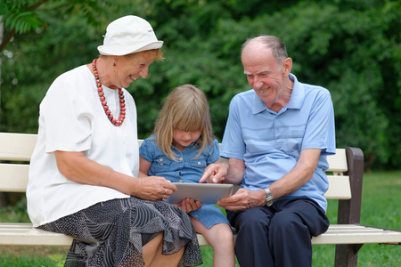 silver surfer: Grandmother, grandfather and granddaughter using tablet computer Stock Photo