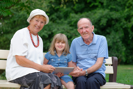 Grandmother, grandfather and granddaughter using tablet computer photo