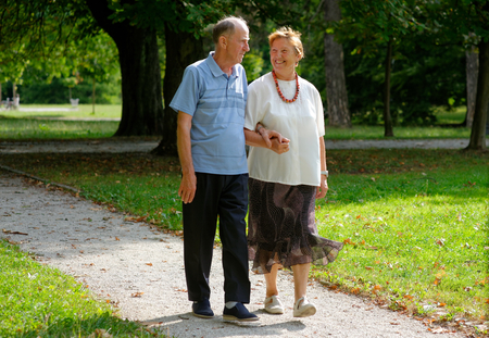 Senior happy couple walking in the park photo