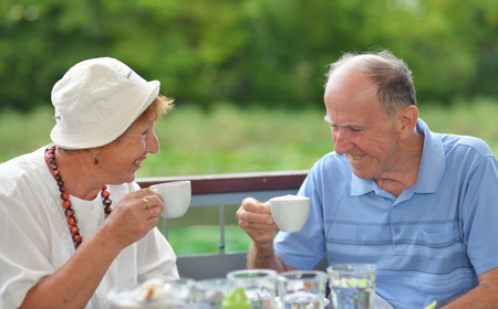 assisted living: Senior Couple Enjoying Snack At Outdoor Cafe