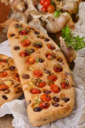 Focaccia with tomato, fresh garlic and black olives   photo