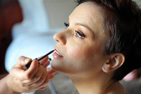 Professional make up artist applying make up to a fashion model   bride