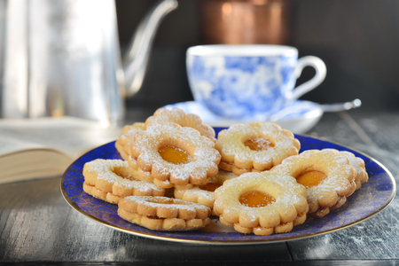 crumbly: Delicious jam cookies with cup of English tea and book