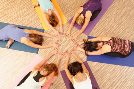 Hände der Frauen Kreis bilden bei Yoga-Klasse