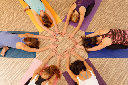 Hands of the women forming circle at Yoga class photo