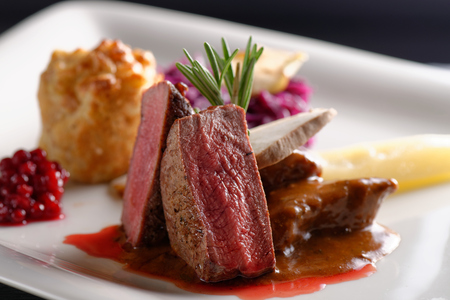 Venison meat steak with red cabbage, cranberries, herbs and Potato