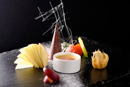 Haute cuisine, dessert Creme brulee and chocolate parfait with fruit Stock Photo