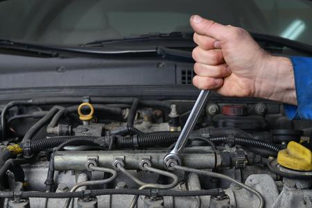 Hand van automonteur met een moersleutel. Auto reparatie. Stockfoto