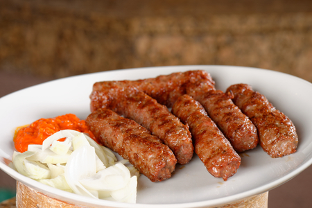 Traditional cevapcici with ajvar paste and onion photo