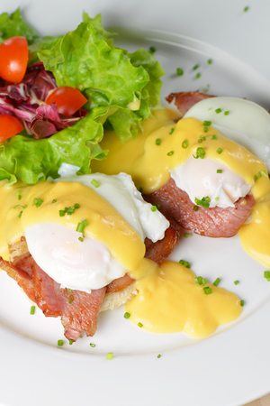 Eggs Benedict- toasted English muffins, ham, poached eggs, and delicious buttery hollandaise sauce photo