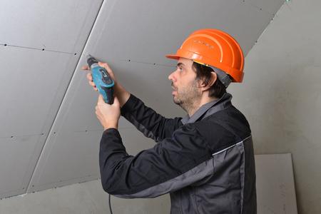 무선 드릴을 사용하여 건식 벽체를 설치하는 사람 스톡 콘텐츠