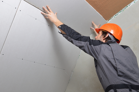 ceiling tile: Man installing drywall gypsum panels