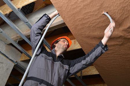 Electrician fitting a cable for ceiling light photo