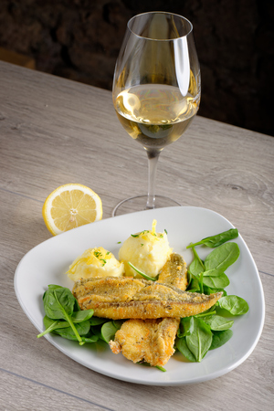 Fried grilled Seabass with spinach, Mash and a glass of white wine photo