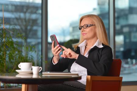 Erfolgreiche und attraktive Frau mittleren Alters im Chat auf dem Handy während ihrer Mittagspause