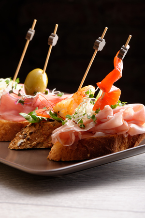 Tapas on Crusty Bread - Selection of Spanish tapas served on a sliced baguette. photo
