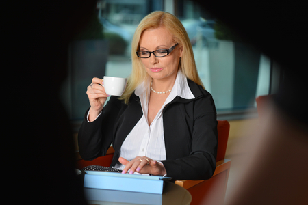 Candid photo of a attractive middle-aged blond businesswoman working at hotel lobby with a tablet pcsmartphone and drinking coffe photo