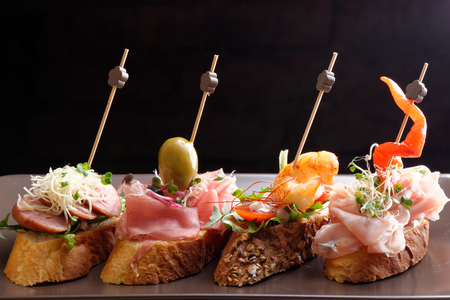 Tapas on Crusty Bread - Selection of Spanish tapas served on a sliced baguette. Imagens - 32672719