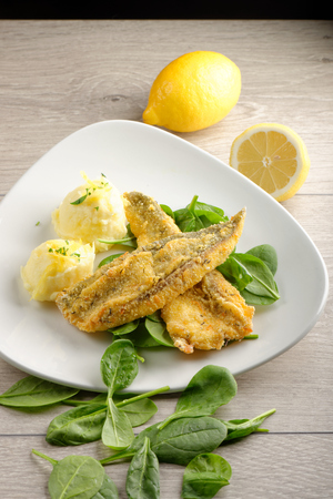 Fillet of sea bream with mashed potatoes, spinach and lemon photo