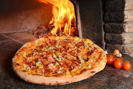 Gebakken lekkere pizza met salami, knoflook en spek in de buurt van de oven Stockfoto