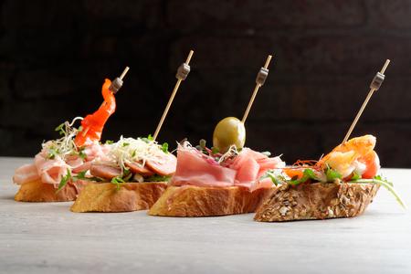 Tapas auf Crusty Bread - Auswahl von spanischen Tapas auf einem Baguette in Scheiben geschnitten serviert.