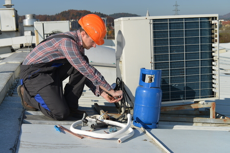 Air Conditioning Repair, young repairman on the roof fixing air conditioning system. Model is actual repairman / electrician. Standard-Bild