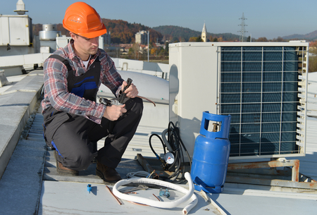 Air Conditioning Repair, young repairman on the roof fixing air conditioning system. Model is actual repairman / electrician. Banco de Imagens