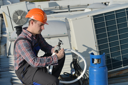 Air Conditioning Repair, young repairman on the roof fixing air conditioning system. Model is actual repairman / electrician. Reklamní fotografie