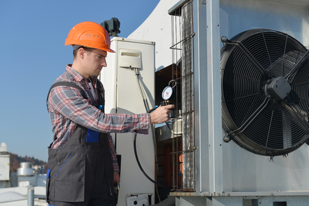 Klimaanlage Reparatur, jungen Handwerker auf der Dachbefestigungsklimaanlage. Modell ist tatsächlich Mechaniker  Elektriker.