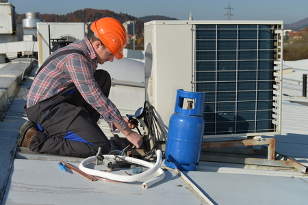 Air Conditioning Repair, young repairman on the roof fixing air conditioning system. Model is actual repairman / electrician. 스톡 콘텐츠