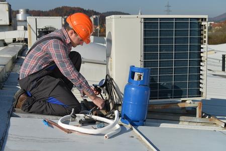 Klimaanlage Reparatur, jungen Handwerker auf der Dachbefestigungsklimaanlage. Modell ist tatsächlich Mechaniker / Elektriker. Standard-Bild - 32913661