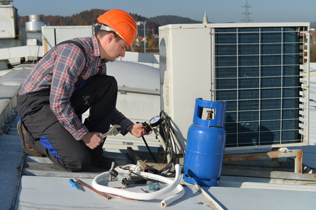 Air Conditioning Repair, young repairman on the roof fixing air conditioning system. Model is actual repairman / electrician. Stock Photo - 32913659