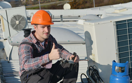 Air Conditioning Repair, young repairman on the roof fixing air conditioning system. Model is actual repairman  electrician.