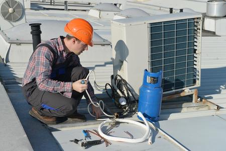 에어컨 수리, 지붕 고정 에어컨 시스템의 젊은 수리공. 모델은 실제 수리  전기입니다. 스톡 콘텐츠