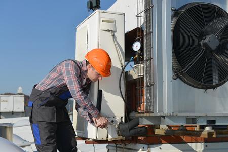 Air Conditioning Repair, jonge reparateur op het dak bevestiging airconditioning systeem. Model is de werkelijke reparateur  elektricien. Stockfoto