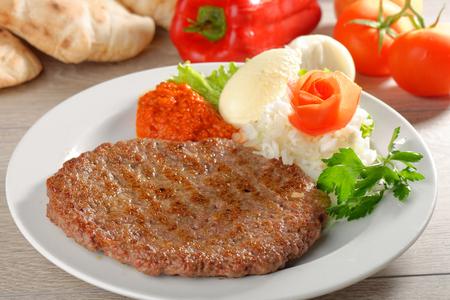 Presliced ??traditionellen Burger Patty genannt pljeskavica, serviert mit Fladenbrot mit etwas Frischkäse Kajmak. Balkan Standard-Bild - 32943588