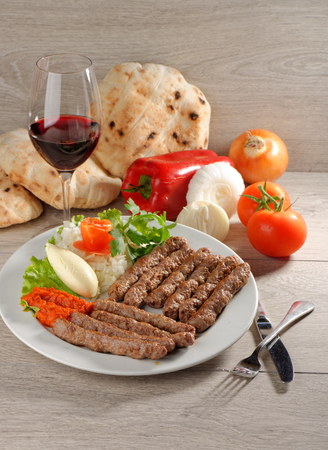 Cevapcici, a small skinless sausage cooked on the barbecue and served with: Lepinja bread, pickled red capsicum and Kajmak cheese. This dish is popular all over the Balkans, with tourists and locals alike.