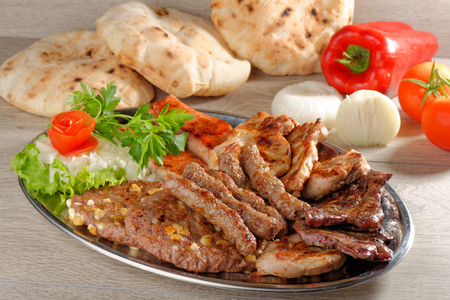 Wholesome platter of mixed meats including grilled steak. Balkan food photo