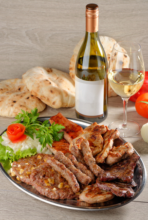 griller: Mixed grill on a plate with excellent wine