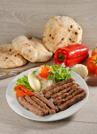 Cevapcici, a small skinless sausage cooked on the barbecue and served with: Lepinja bread, pickled red capsicum and Kajmak cheese. This dish is popular all over the Balkans, with tourists and locals alike. photo