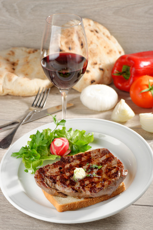 Grilled steak on toast bread, served with onion and vegetable and a glass of good wine photo