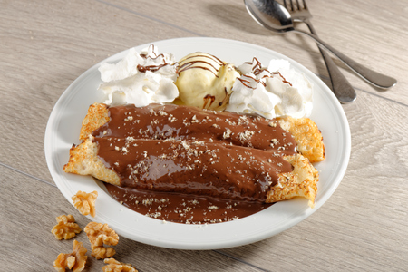 close up of two french style crepes, served with chocolate, walnuts and ice cream, shallow dof. photo