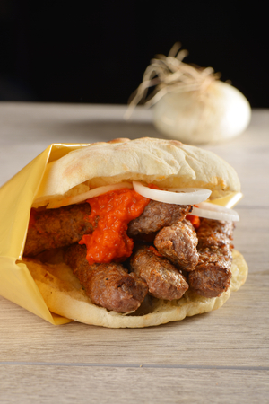 Traditional cevapcici with ajvar in the grilled roll Imagens
