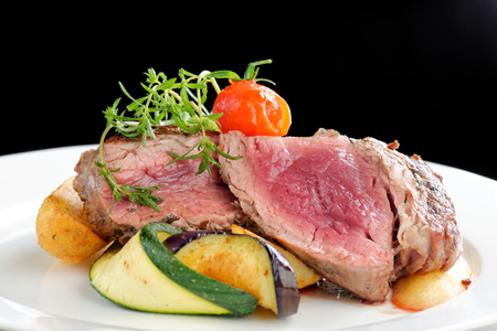 medium close up: Grilled bbq steaks with fresh herbs, potato, vegetable and tomatoes